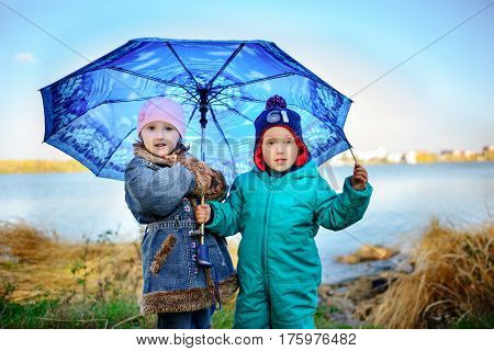 Little Girl And Boy With Umbrella Playing In The Rain. Kids Play Outdoor By Rainy Weather In Fall. A