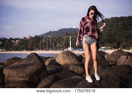 Outdoor summer stylish portrait of beautiful elegant woman with perfect fit body and long legs walking along on the beach, wear summer outfit, posing at sunny day on the beach of sand.