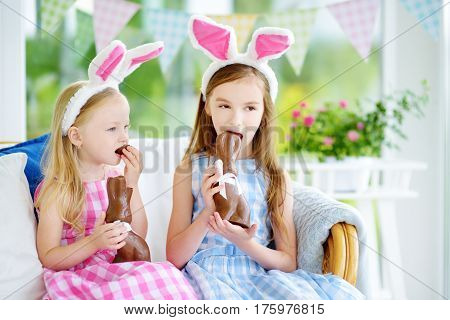 Two Cute Little Sisters Wearing Bunny Ears Eating Chocolate Easter Rabbits. Kids Playing Egg Hunt On