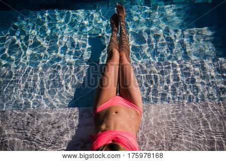 Sexy body of beautiful woman. Girl relaxing in a poll at summer