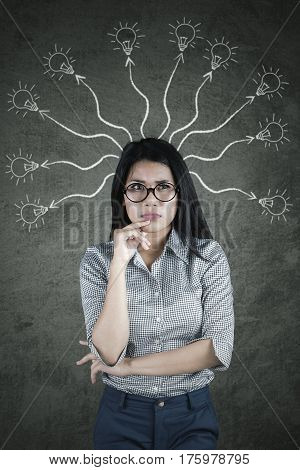 Pensive businesswoman looking at the camera while thinking with many arrows and bulbs above her head