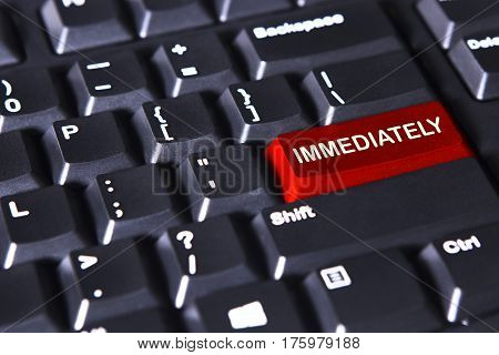 Closeup of modern keyboard with text of immediately on the red button