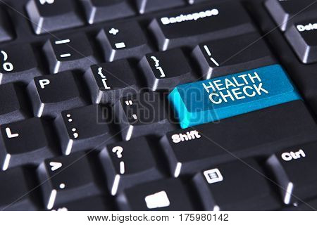 Close up of computer keyboard with text of health check on the blue button