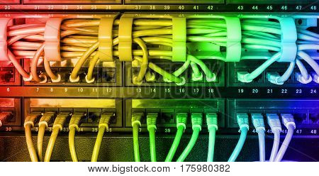 Server rack with colorful internet patch cord cables connected to black patch panel in server room horizontal with rainbow gradient