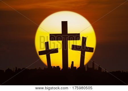 Silhouette of three crucifixes above the city with a golden sun shot at sunset time