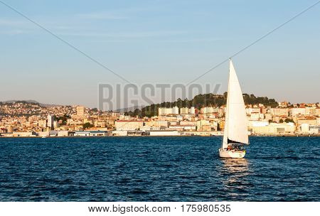 A sailboat approaching Vigo harbor (Galicia Spain) at sunset on a summer day