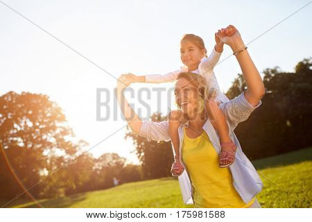 Cheerful mother with daughter enjoying in nature