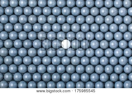 White Airsoft Ball Is Among Many Black Balls. Background Of 6Mm Bbs