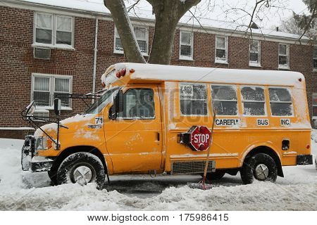 BROOKLYN, NEW YORK - FEBRUARY 9, 2017: School bus under snow in Brooklyn, NY after massive Winter Storm Niko strikes Northeast.