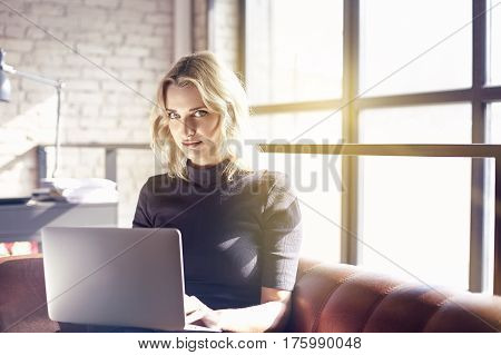 Beautiful blonde businesswoman sitting in sunny office working on laptop. Concept of young people working mobile devices. Sunshine throw windows on background daylight.