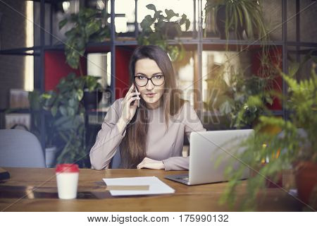 Beautiful girl wearing eye glasses in coworking studio talking by smartphone. Concept of young people working with mobile gadgets. Modern office blurred on background. Horizontal