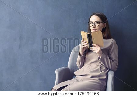 Beautiful businesswoman sitting in loft office reading vintage book. Opened book brown cover. Dark blue wall background day light