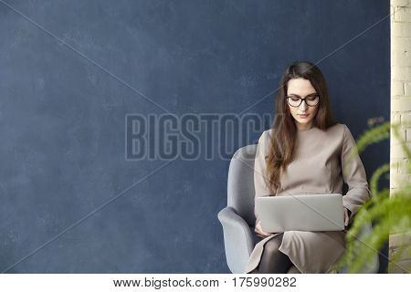 Beautiful businesswoman working on laptop while sitting in modern loft office. Dark blue wall background day light