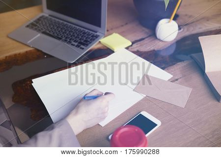 Businesswoman with documents paper sheet in loft modern office working on laptop computer. Team working business people. Space for design layout