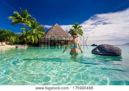 Young beautiful woman in blue bikini inside tropical infinity pool, Tahiti