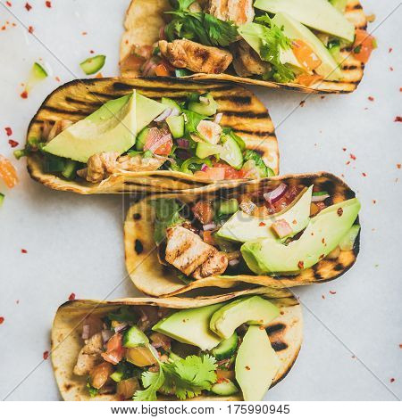Healthy corn tortillas with grilled chicken, avocado, fresh salsa, limes over light grey marble background, top view, square crop. Healthy food, gluten-free, allergy-friendly, weight loss concept