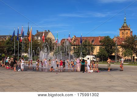 Colmar, France - 18 July, 2014: people at the fountain on Place Rapp square. Colmar is the third-largest commune of the Alsace region in north-eastern France, renowned for its well preserved old town, numerous architectural landmarks and museums.