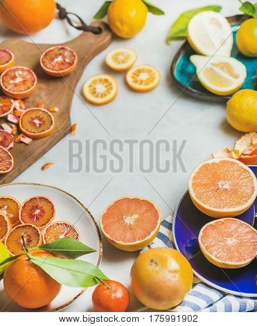 Natural fresh citrus fruits in colorful ceramic plates and wooden rustic cutting board over grey marble table background, selective focus, copy space
