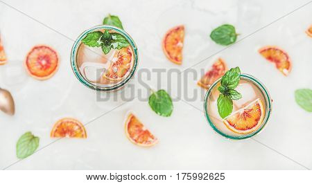 Blood orange fresh summer lemonade with ice and mint in glasses, light grey marble background, selective focus, top view