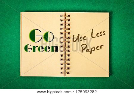 Go Green. Use Less Paper in recycle paper notebook on green background.