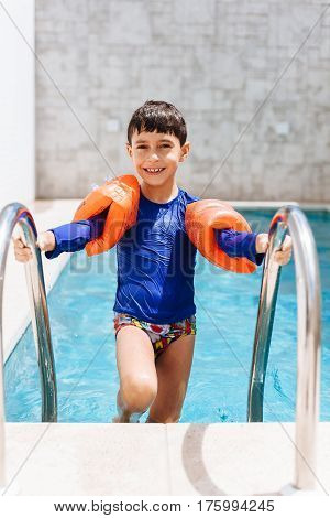 Sweet Little Boy In Swimsuit With Arm Float In The Pool