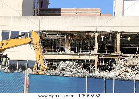 Yellow bulldozer deconstructing building. Construction industry concept.
