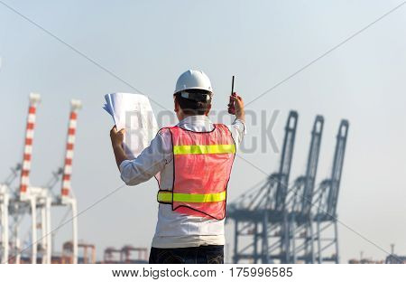 The man engineer working with container Cargo freight ship in shipyard at dusk for Logistic Import Export background