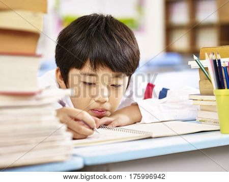 tired and bored asian elementary school boy doing homework in classroom head resting on desk.