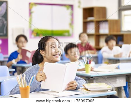 asian elementary school student smiling in class.