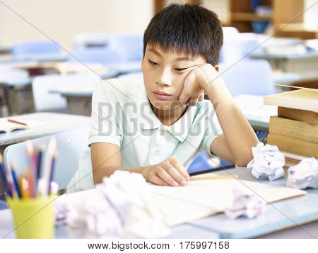 frustrated asian pupil sitting at desk dazing