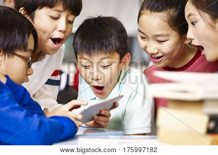 group of asian elementary school children gathering around playing game together using tablet during break.