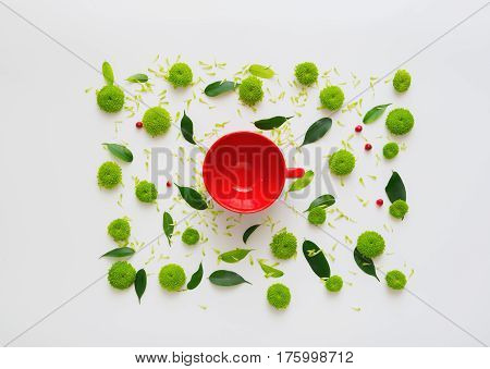 Cup for coffee or tea with pattern with petals of chrysanthemum flowers, ficus leaves, hearts and ripe rowan on white background. Overhead view. Flat lay.