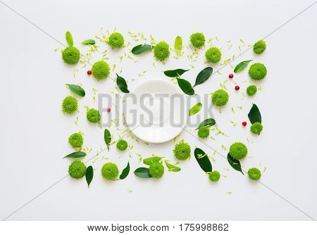 Plate with pattern with petals of chrysanthemum flowers, ficus leaves, hearts and ripe rowan on white background. Overhead view. Flat lay.