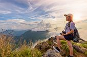 Hiker asian young woman happy with camera backpack and caps looking beautiful landscape nature of mountain and colourful sky at sunset on viewpoint Phu Chi Fa Forest Park Chiang Rai Thailand poster
