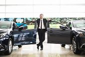 Confident smiling car salesman at the showroom he is standing near open cars doors of luxury cars poster