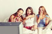 friendship, people, pajama party, entertainment and junk food concept - happy friends or teenage girls eating pizza and watching movie or tv series at home poster