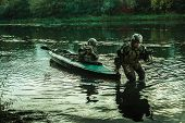Covert landing. Pair of armed operators with painted faces disembarking river coast from military kayak . Diversionary mission under cover of darkness poster