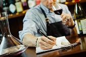 Male sommelier tasting red wine and making notes at bar counter. Bottle of wine nearby. Professional expert appreciates quality of alcoholic beverage, degustation process poster