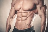 Handsome caucasian sexy fitness model in gym close up abs concept man on diet shirtless training six pack healthcare lifestyle crunch poster