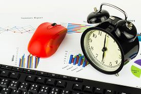 Keyboard and alarm clock calculations savings finances and economy concept.