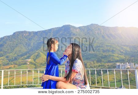 Happy Asian Mother And Daughter On Balcony At Hillside.