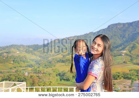 Asian Mother Carrying Daughter On Balcony At Hillside And Pointing Camera.