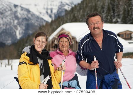 A group of three outdoor in a winter setting. The active people are about to go crosscountry skiing.