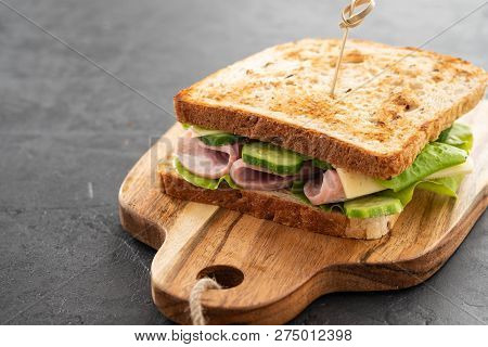 Close-up Photo Of A Club Sandwich. Sandwich With Meet, Prosciutto, Salami, Salad, Vegetables, Lettuc