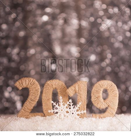 Inscription 2019 New Year In The Snow On A Bright Gray Background With Bokeh Effect