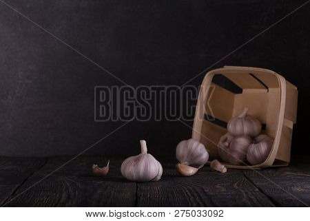 Basket Of Garlic And Separate Garlic Cloves On The Boards On A Dark Background In A Dark Key