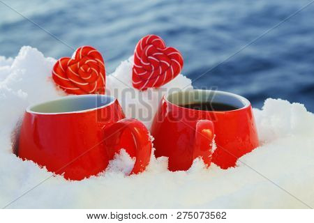 Two Red Mugs With Hot Tea Or Coffee And Lollipops Hearts In The Snow. Picnic On A Frosty Sunny Day O