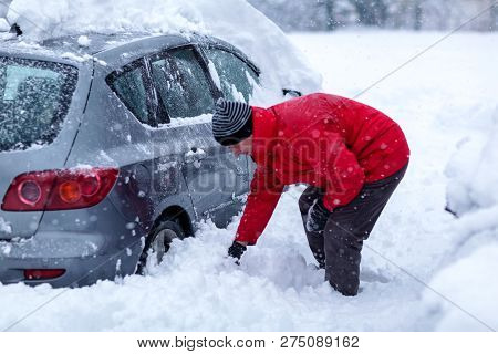 Young Man Is Cleaning Clean Off His Car Of Snow Cover By Brush. Snow Covered Car.
