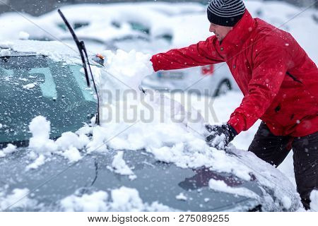 Winter Problems Of Car Drivers. A Man Brushing Snow From The Car. Young Man Removing Snow From Car.