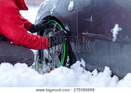 Snow Chains On The Wheels Of Car. Young Man Tries To Put Snow Chains On Tires Clutching The Snow Cha